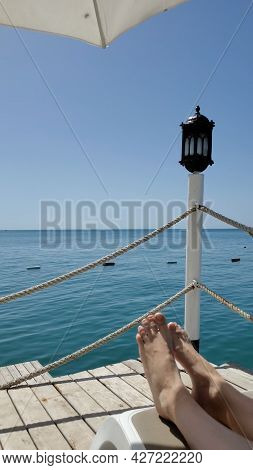 Female Barefoot Legs On Sunbed With Blue Sea Water Background. Resting On Chaise Lounge At Sea Pier