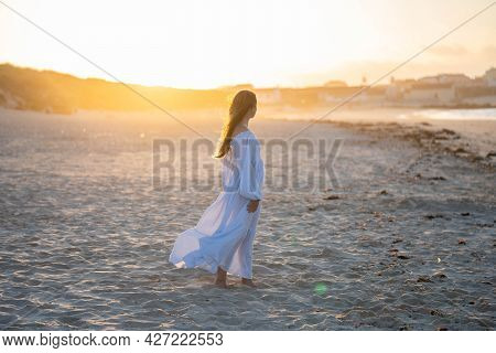 Girl On The Beach Against The Backdrop Of The Setting Sun. Concept: Lightness, Airiness