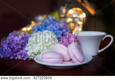Pink Marshmallow On A White Saucer With Multicolored Hydrangea Flowers And A Cup Against The Backgro
