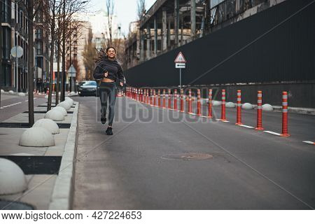 Cheerful Female Jogger With Cornrows Running Ahead