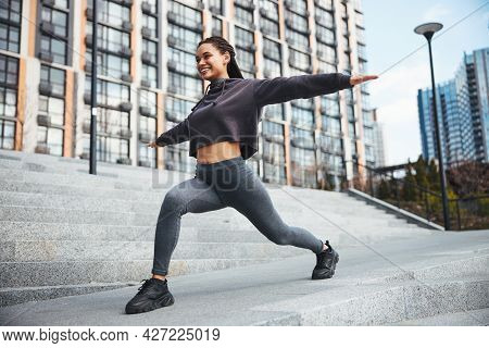 Joyous Sportswoman With Cornrows Exercising On The Concrete Stairs