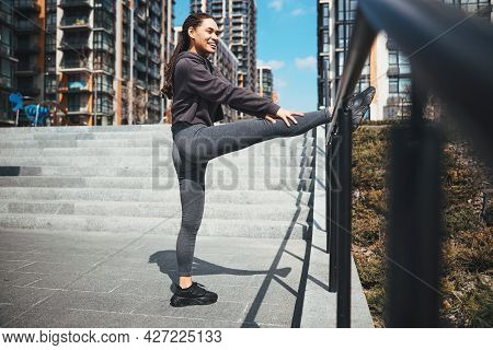 Sportswoman Performing A Leg Stretching Exercise Outdoors