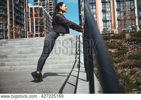 Joyous Female Athlete Working Out On The Staircase Outdoors