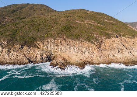 Sea water waves break over the island