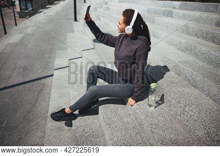 Joyous Woman Taking Selfies On The Concrete Steps Outside