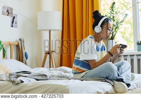 Side View Portrait Of Trendy Teenage Girl Playing Mobile Game Vi Smartphone While Sitting On Bed In