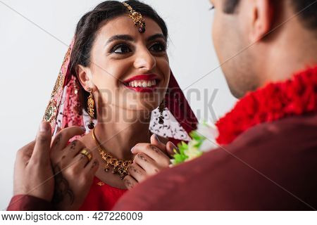 Happy Indian Bride In Headscarf Looking At Blurred Bridegroom Isolated On White