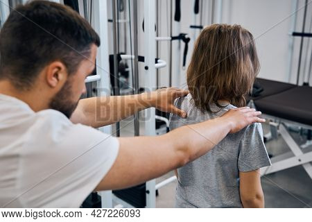 Massage Therapist Treats Girl In Medical Rehab Center Back View. Chiropractor Checks Spine, Neck