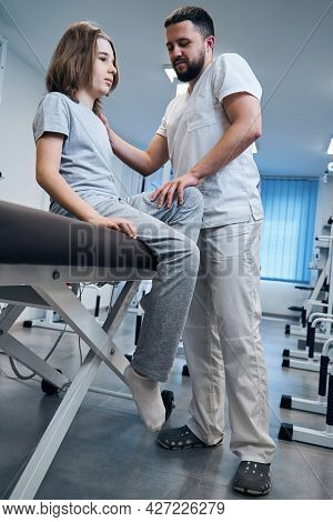 Osteopath Doctor Checks Knee Joint Of Girl Sitting On Massage Bed Closeup. Pediatric Physiotherapist