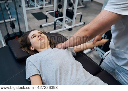 Girl Gets Chiropractic Shoulder Therapy From Man Physical Therapist In Sports Injury Rehab Clinic