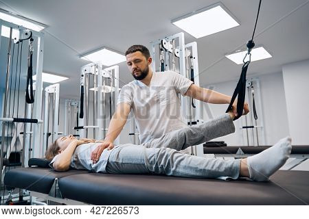 Girl Lying On Physical Therapy Bed, Doing Exersises On Elastic Strength Machines With Chiropractor