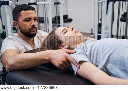 Close Up Pediatric Physiotherapist Treats Young Girl On Rehabilitation Decompression Machines