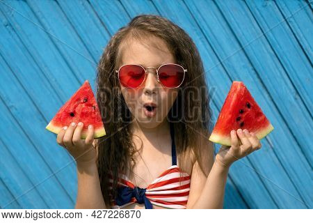 A Beautiful Curly-haired Girl With An Open Mouth And A Surprised Face Holds Two Juicy Sweet Pieces O