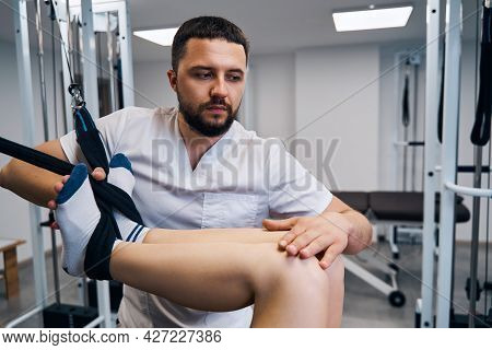 Strength Training Of Young Woman Legs, Knee On Flexible Simulator In Rehabilitation Center Closeup