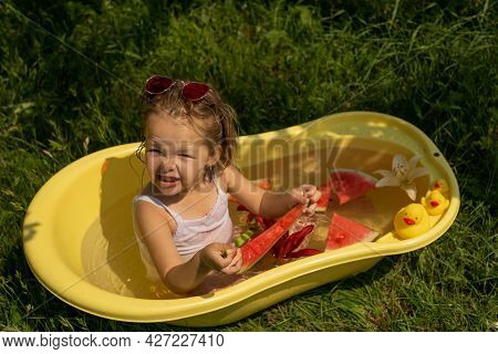 A Little Girl Bathes In A Yellow Bath With Flowers And Ducks In Nature And Eats A Juicy Sweet Waterm