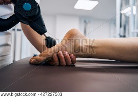 Close-up Of Masseur Rubbing Woman Foot With Massage Percussion Device In Rehab Clinics Therapy Room