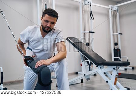Professional Physiotherapist Bends Woman Knee With Rehabilitation Equipment Tether In Rehab Center