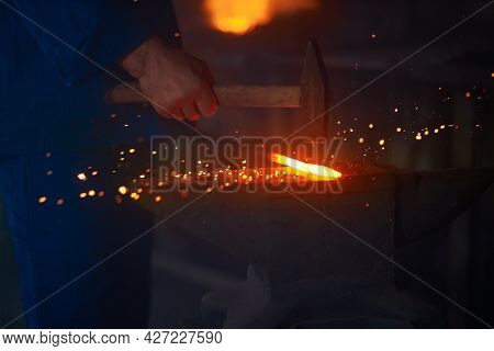 Experienced Blacksmith Manually Forging Molten Metal With Hammer On Anvil. Close Up Of String Male H
