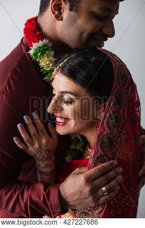 Bridegroom Hugging Pleased Indian Bride In Headscarf Isolated On Grey