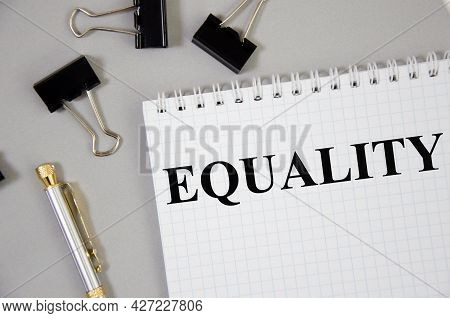 Equality Word Written On Gray Background With Pencils And Paper Clips