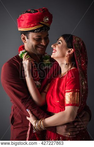 Cheerful Indian Man In Turban Hugging Happy Bride In Traditional Headscarf Isolated On Grey