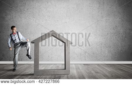 Determined Businessman Going To Break With Kick House Concrete Figure