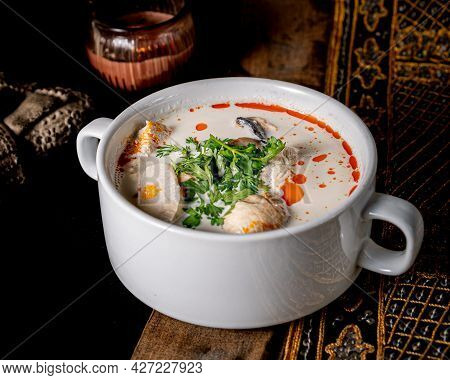 Great Tom Kha With A Base Of Coconut Cream, Mushrooms And Tofu Served In A Deep White Plate.