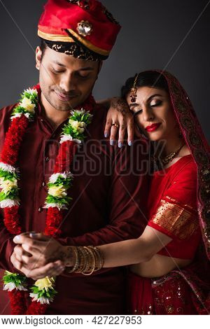 Indian Man In Turban Holding Hands With Happy Bride In Traditional Headscarf Isolated On Grey