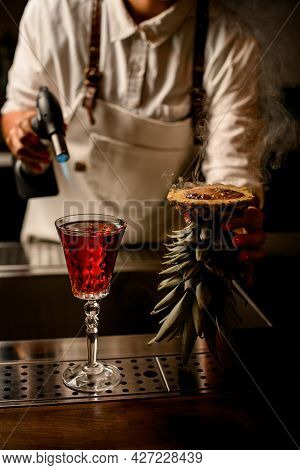 Woman Bartender Holds Pineapple With Burnt Brown Caramel Crust Near Glass Of Drink