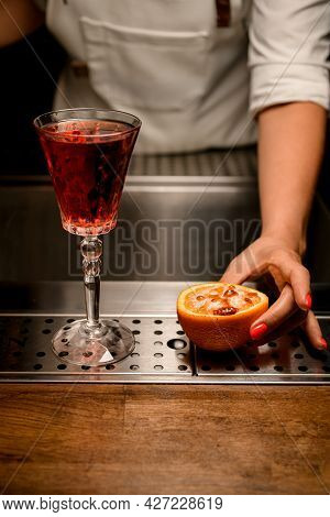 Glass With Drink And Half Orange With Burnt Caramel Crust On Bar Counter