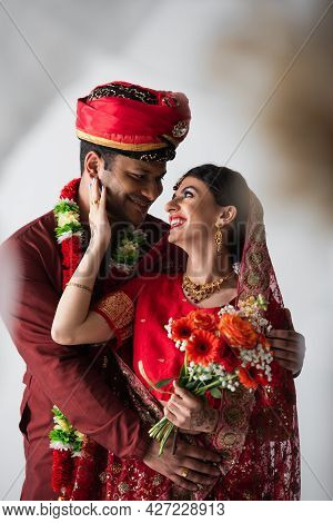 Happy Indian Man Hugging Cheerful Bride In Headscarf And Sari With Bouquet Of Flowers On White