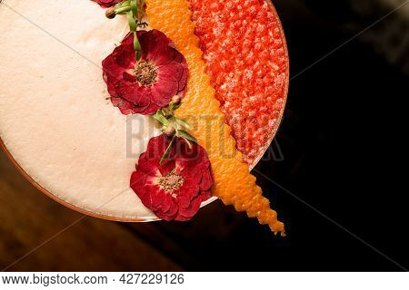 Close-up Of Beautiful Dried Flowers And Orange Peel Decorating Glass Of Frothy Cocktail
