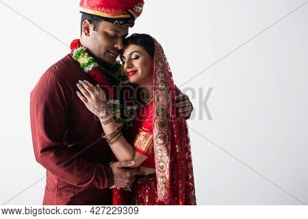 Happy Indian Couple Of Husband And Wife In Traditional Clothing Hugging Isolated On Grey