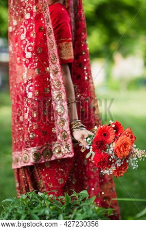 Cropped View Of Indian Bride In Red Sari And Traditional Headscarf With Ornament Holding Flowers
