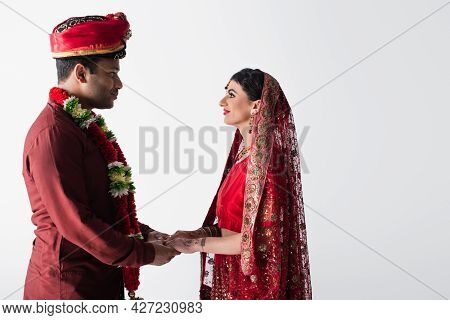 Side View Of Happy Indian Couple Of Husband And Wife In Traditional Clothing Holding Hands Isolated