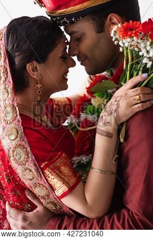 Side View Of Pleased Indian Man And Woman Hugging On Wedding Isolated On White