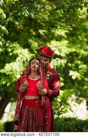 Happy Indian Man In Turban Hugging Bride With Mehndi In Sari And Headscarf
