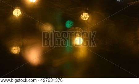 Intentional Motion Blur Lights. Blurry Dirty Glass Window With Golden And Green Bokeh Lights Of Nigh