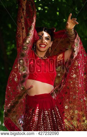 Happy Indian Bride In Red Sari And Traditional Headscarf With Ornament Posing Outside