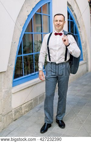 Handsome Mature Caucasian Man Groom In A White Shirt With A Red Bow Tie And In Suspenders Holds A Ja