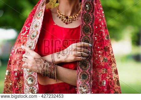 Partial View Of Young Indian Bride In Red Sari Adjusting Headscarf With Ornament
