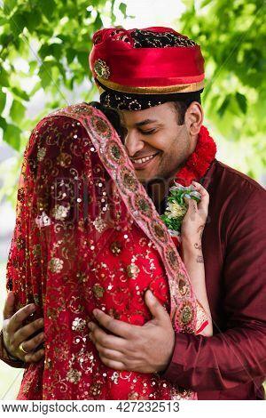 Indian Bride In Headscarf Wearing Floral Garland On Happy Bridegroom