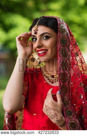 Happy Young Indian Bride In Red Sari And Headscarf With Ornament