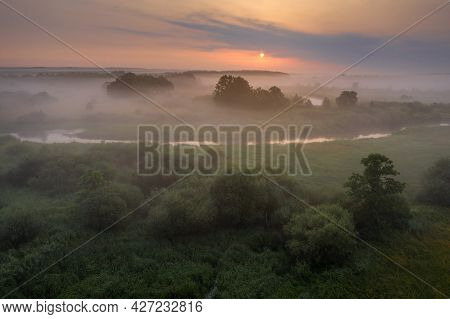 Landscape Aerial View Of River And Woodland. Misty Sunrise Above The River. Fog Above The Winding Ri