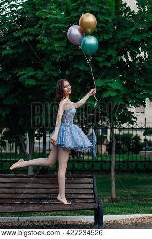 A Young Woman In A Blue Dress Walks Barefoot On A Wooden Bench And Holds Flying Balloons, Pretending