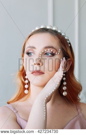 Close-up Portrait Of A Pale-skinned Caucasian Woman With Pearl Makeup In The Form Of A Curved Line O