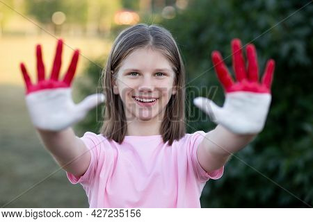 Love Indonesia. Child Girl Show Hands Painted In Indonesia Flag Colors. Indonesian Patriotism Concep