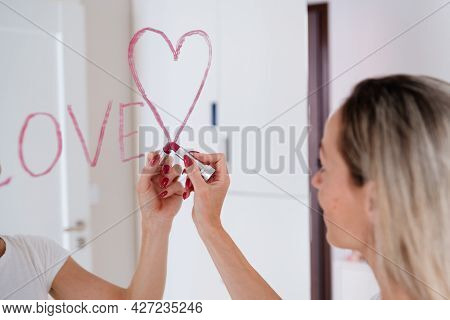 A Woman Draws The Inscription Love And A Heart With Lipstick On The Mirror.