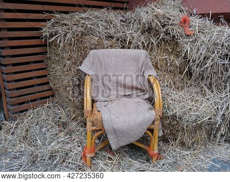 Wooden Wicker Chair Covered With Rug Near Pile Of Hay Stacks. Farmers Place For Rest