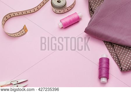 Tailor's Work Desk. Sewing Accessories And Fabric On A Pink Background. Sewing Threads, Needles, Fab